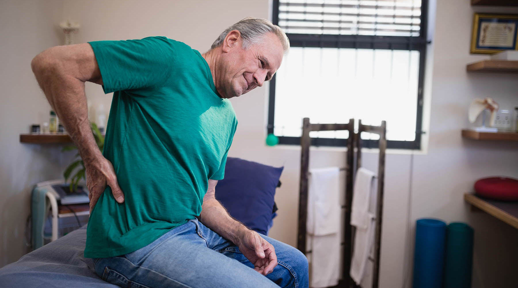 Older man in green shirt at doctor's office dealing with pain from tension myalgia