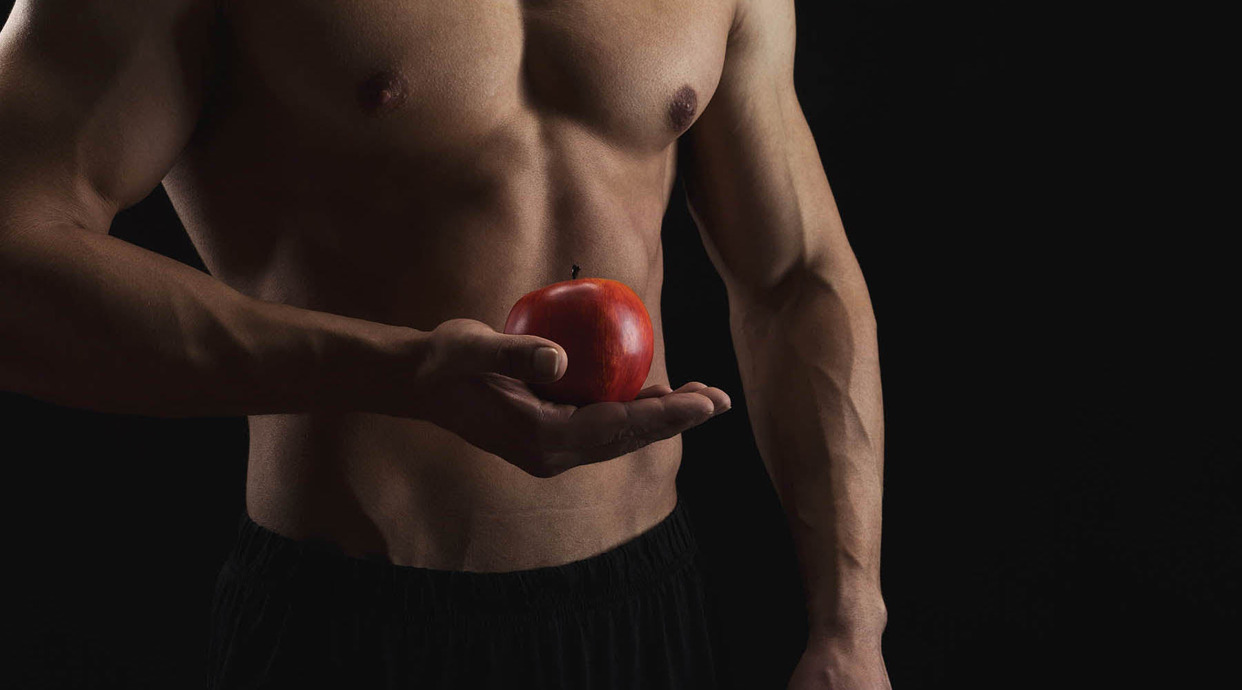 Healthy man's bare torso holding an apple in his right hand