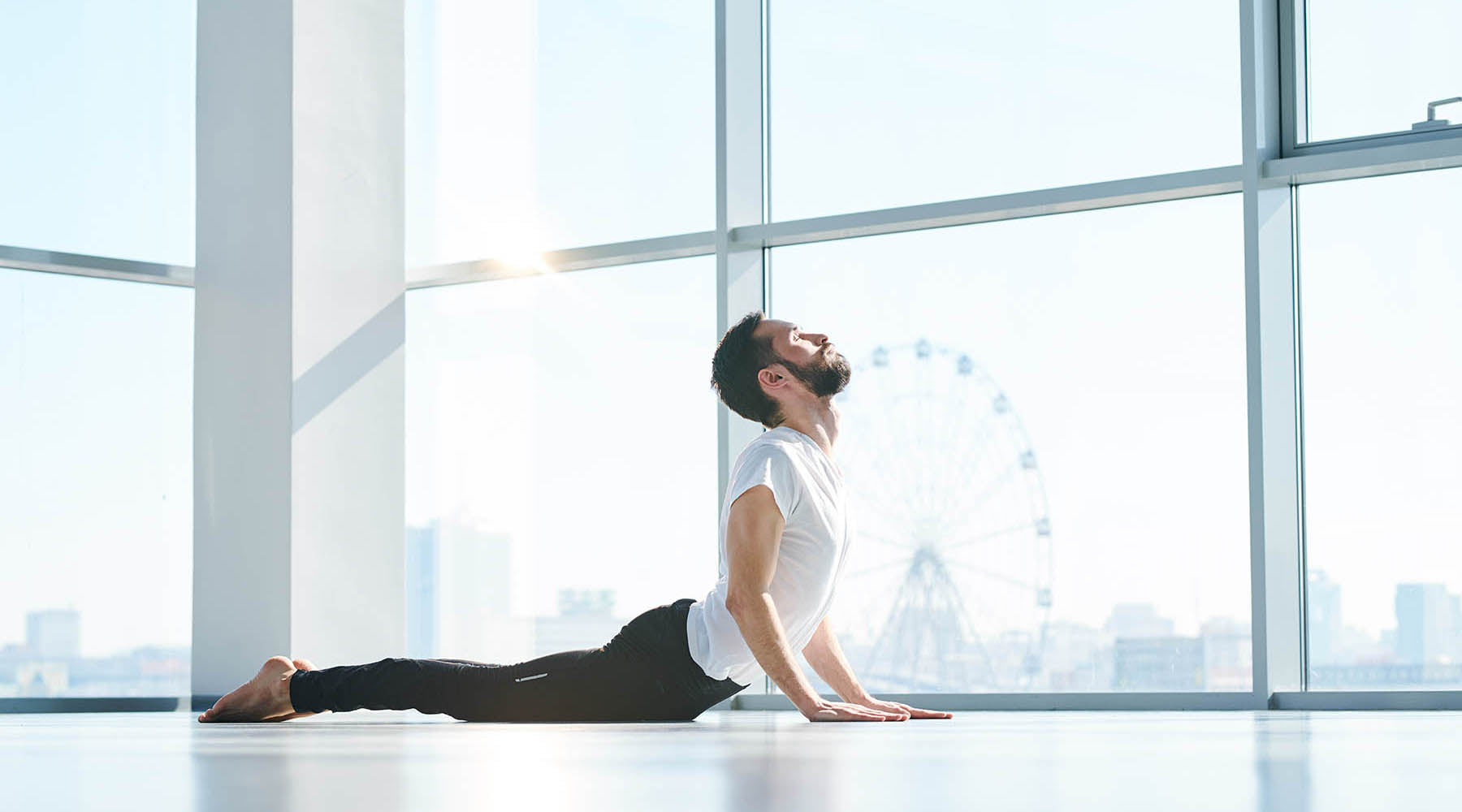 Man in white shirt and black pants performing Kegel exercises in a room with big windows
