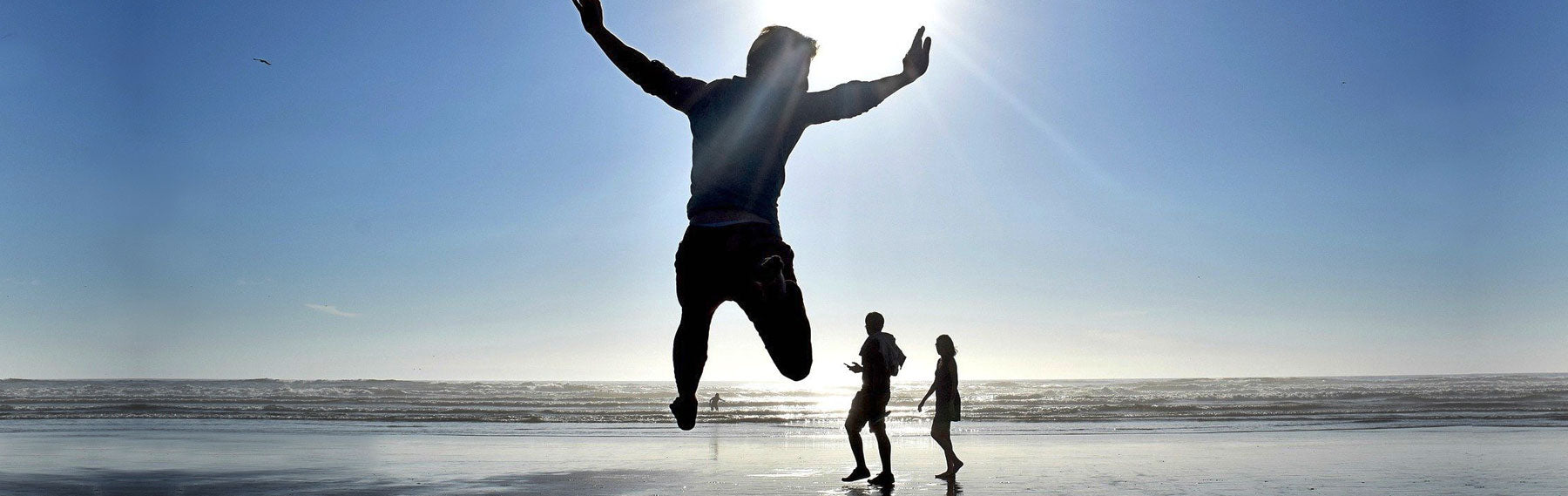 Man jumping with arms out on beach with sun behind him with a couple and the sun behind him