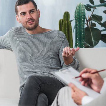 Man in 30s on couch talking to doctor about erectile dysfunction