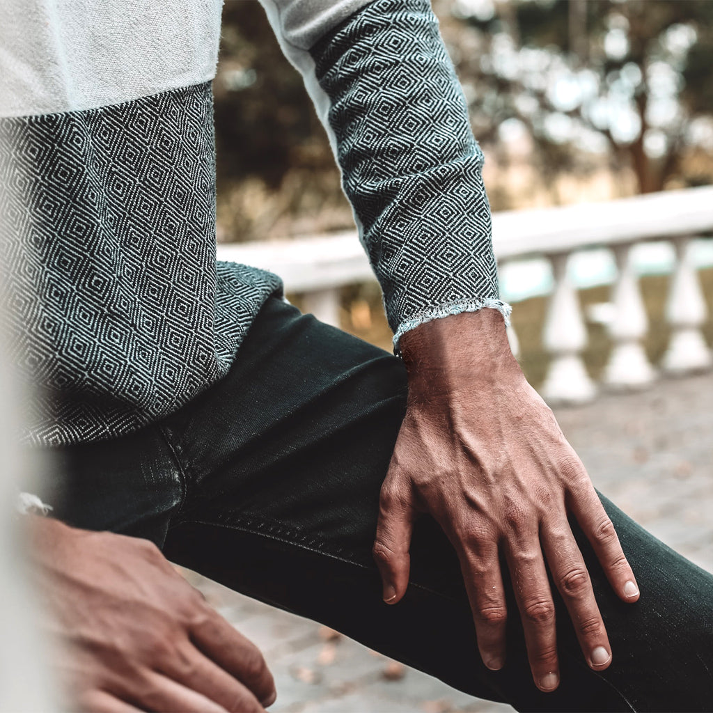 Midsection photo of man in gray two-tone sweater and black jeans with hands on inner thighs