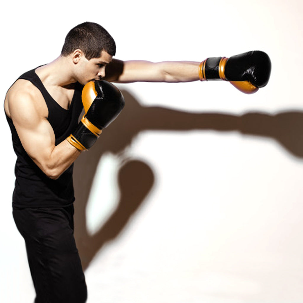 You man in black tank top, black jeans and boxing gloves throwing a punch