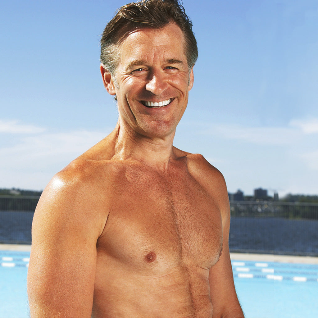 Heathy looking late-middle-age man standing with shirt off in front of pool