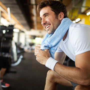 Healthy man in 30s with blue towel around neck sitting at gym