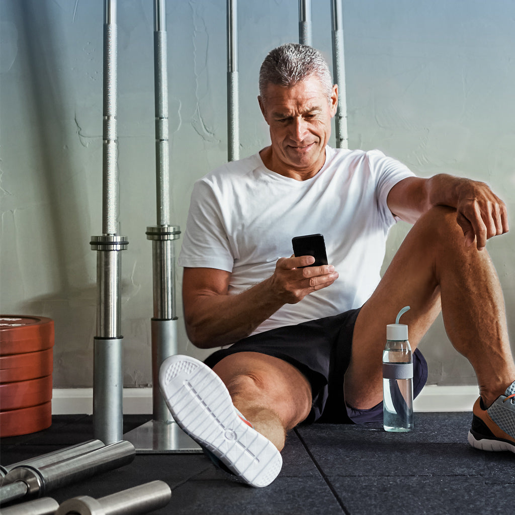Fit older man in white t-shirt and black shorts sitting by empty barbells holding phone with water bottle on floor