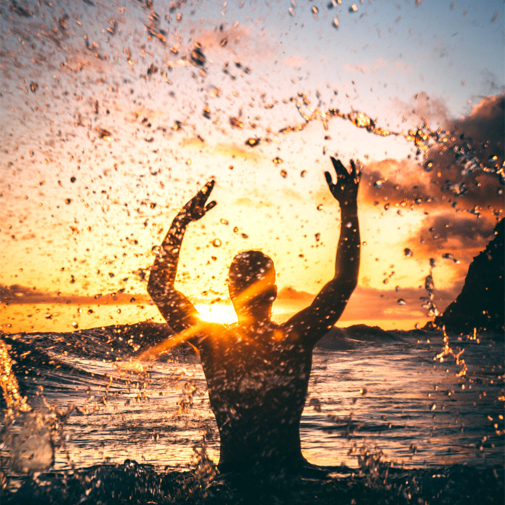 Man in water with hands in the air, splashing water at sunset