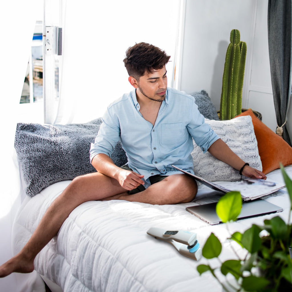 Man with shirt but no pants sitting on bed with notebook, laptop & Viberect