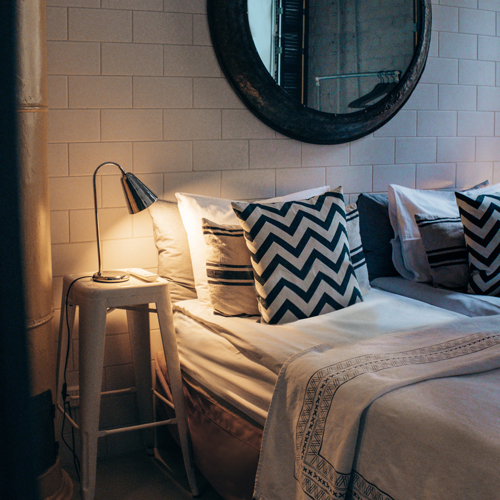 Bedroom scene with white tile wall, round mirror, white bed sheets and pillows