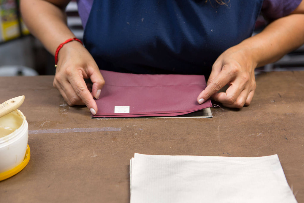 skilled worker putting final touches on assembly of Burgundy wallet