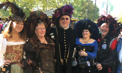 A couple of men wearing Tudor style feathered Hats amongst the beauties at the Maryland Renaissance Festival