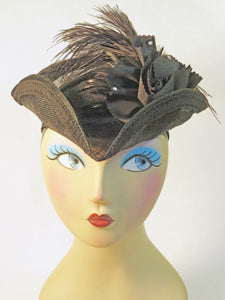 A classic TriCorn Hat in lightweight Sinamay material, this all black hat is decorated with a silk rose and spray of feathers.