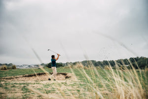 Golfer wearing the Fescue Golf Signature Merino Shirt hitting out of a bunker on a golf course