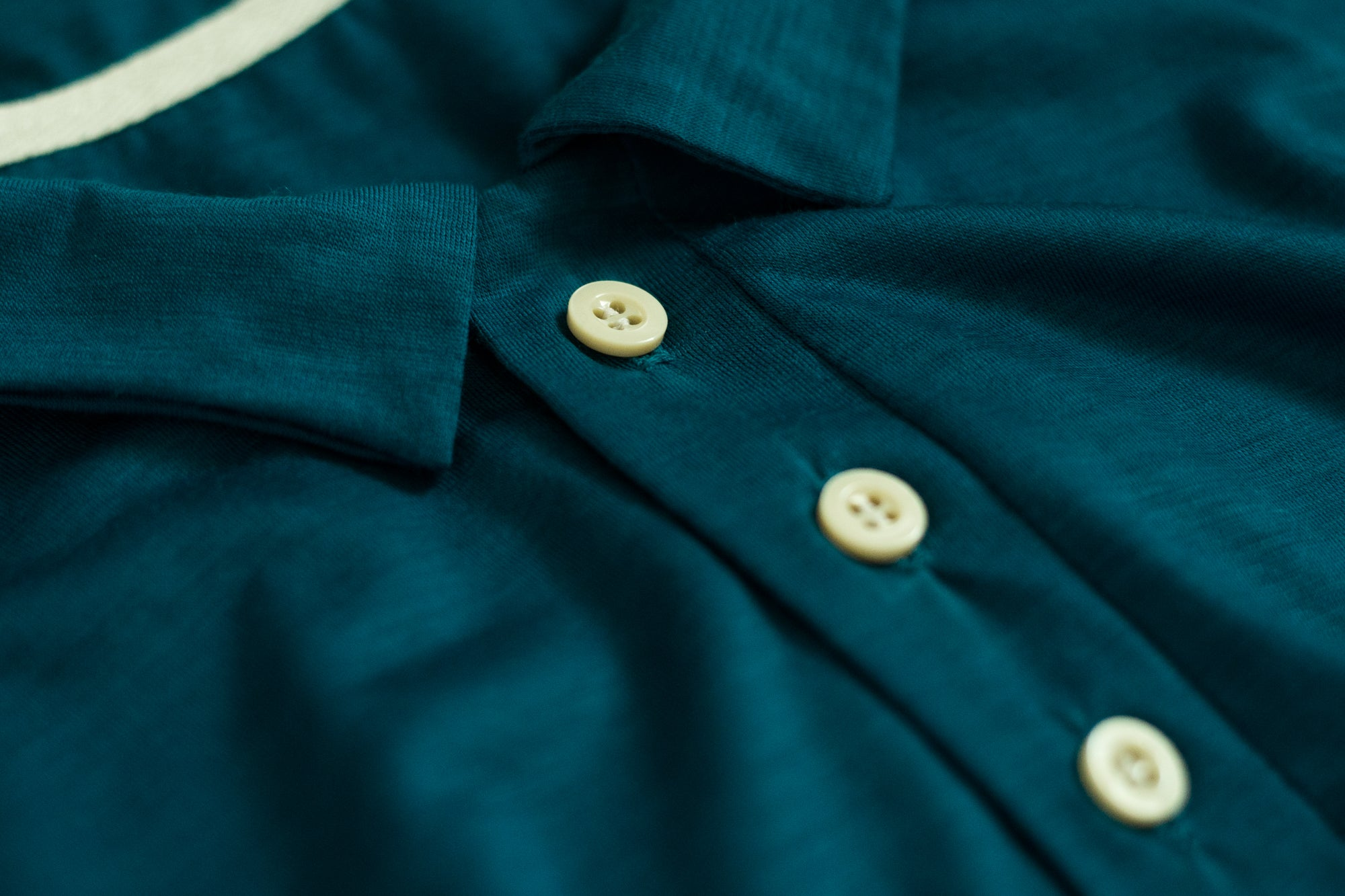 Close up of the 100% Merino Wool Fabric and made in Britain buttons used for the Signature Merino Golf Polo Shirt
