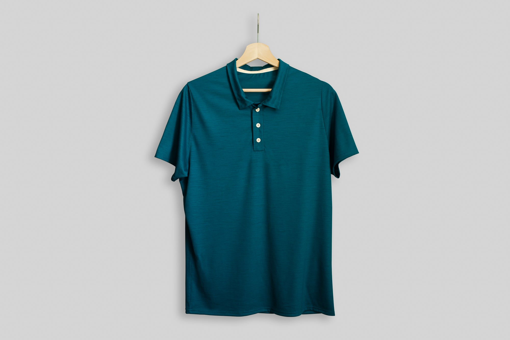 Dragonfly Signature Merino Golf Polo Shirt displayed on a hanger
