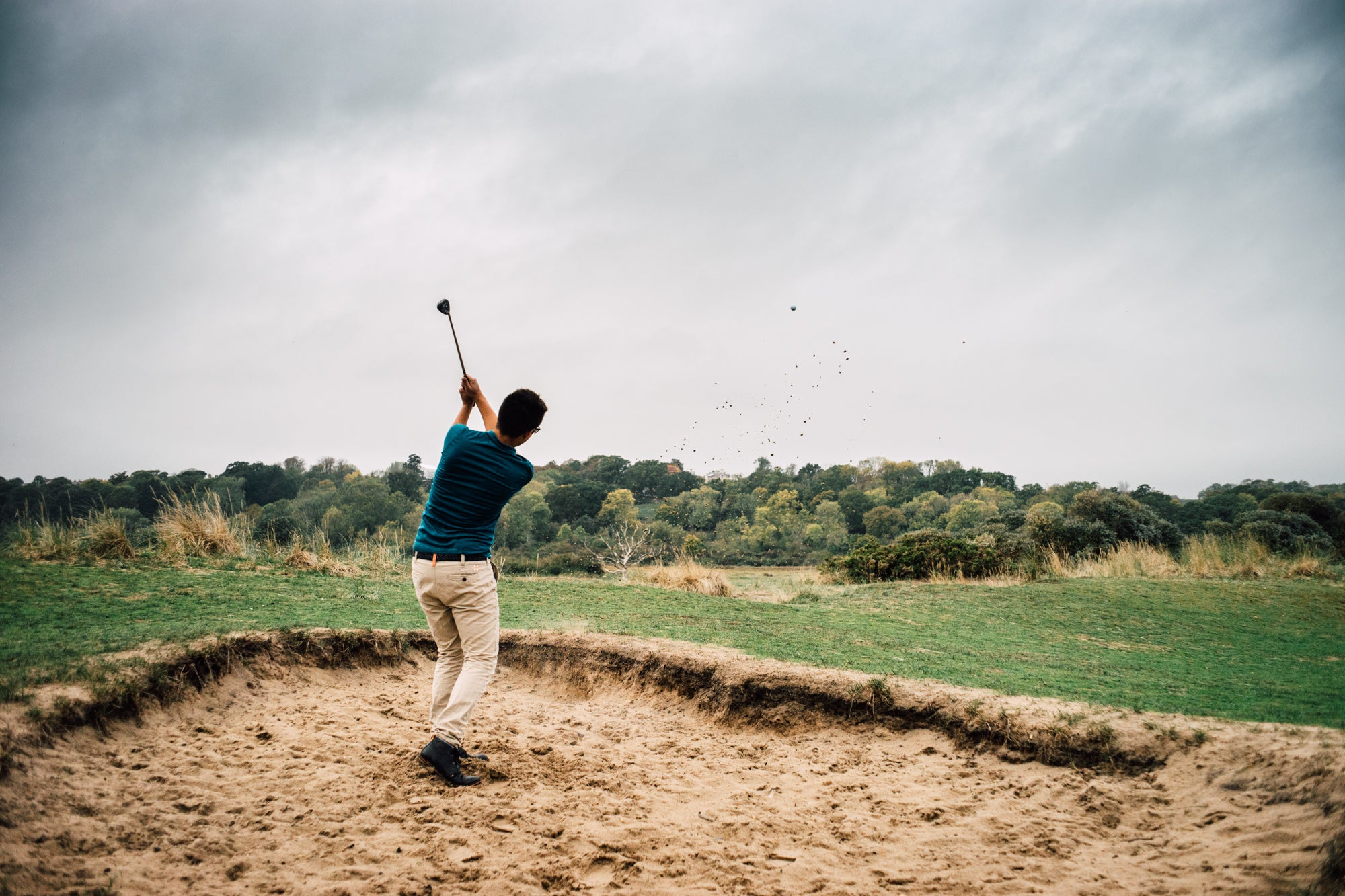 Golfer hitting from a bunker whilst wearing the Signature Merino Golf Polo Shirt on the former linksland site of the Royal Isle of Wight Golf Club