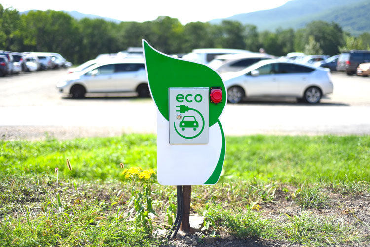 Eco sign in front of a parking lot full of electronic cars.