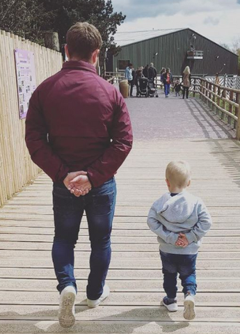Young child mimicking his dad, both walking with hands behind back