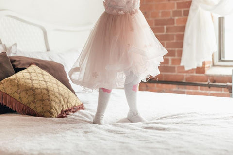 Little girl in a pink dress standing on a bed
