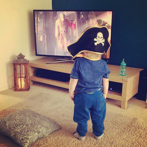 Little boy dressed as a Pirate watching TV