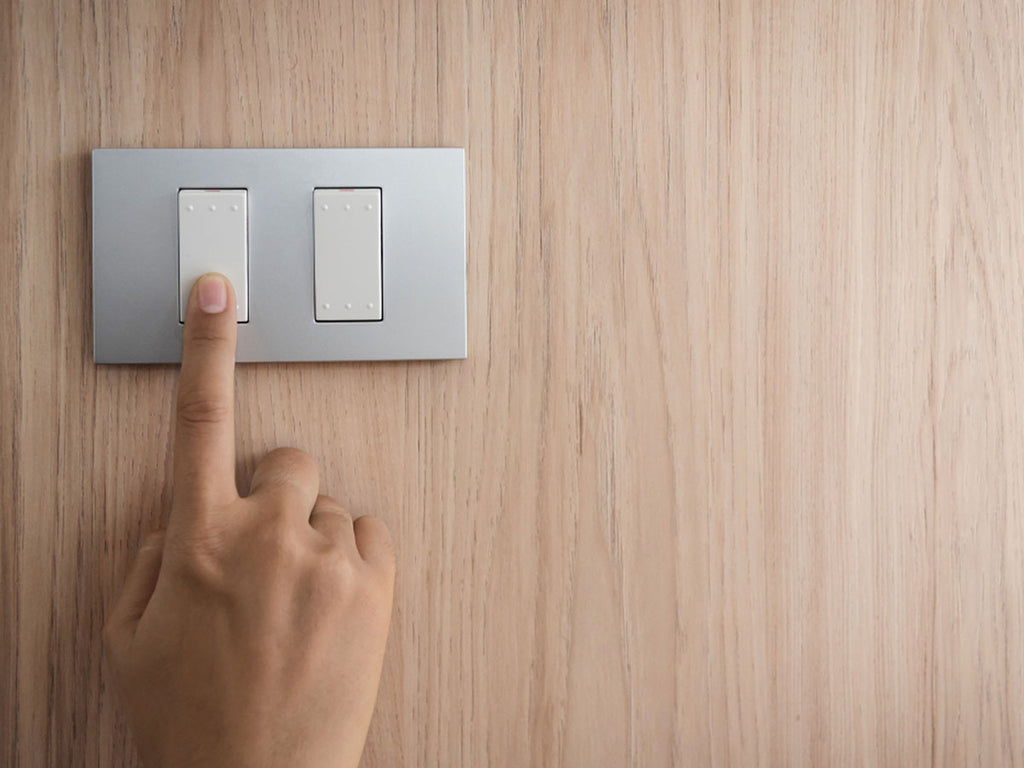 Image of someone turning off a light switch with a wood wallpaper background