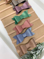 Set of 10 faux leather baby bows.