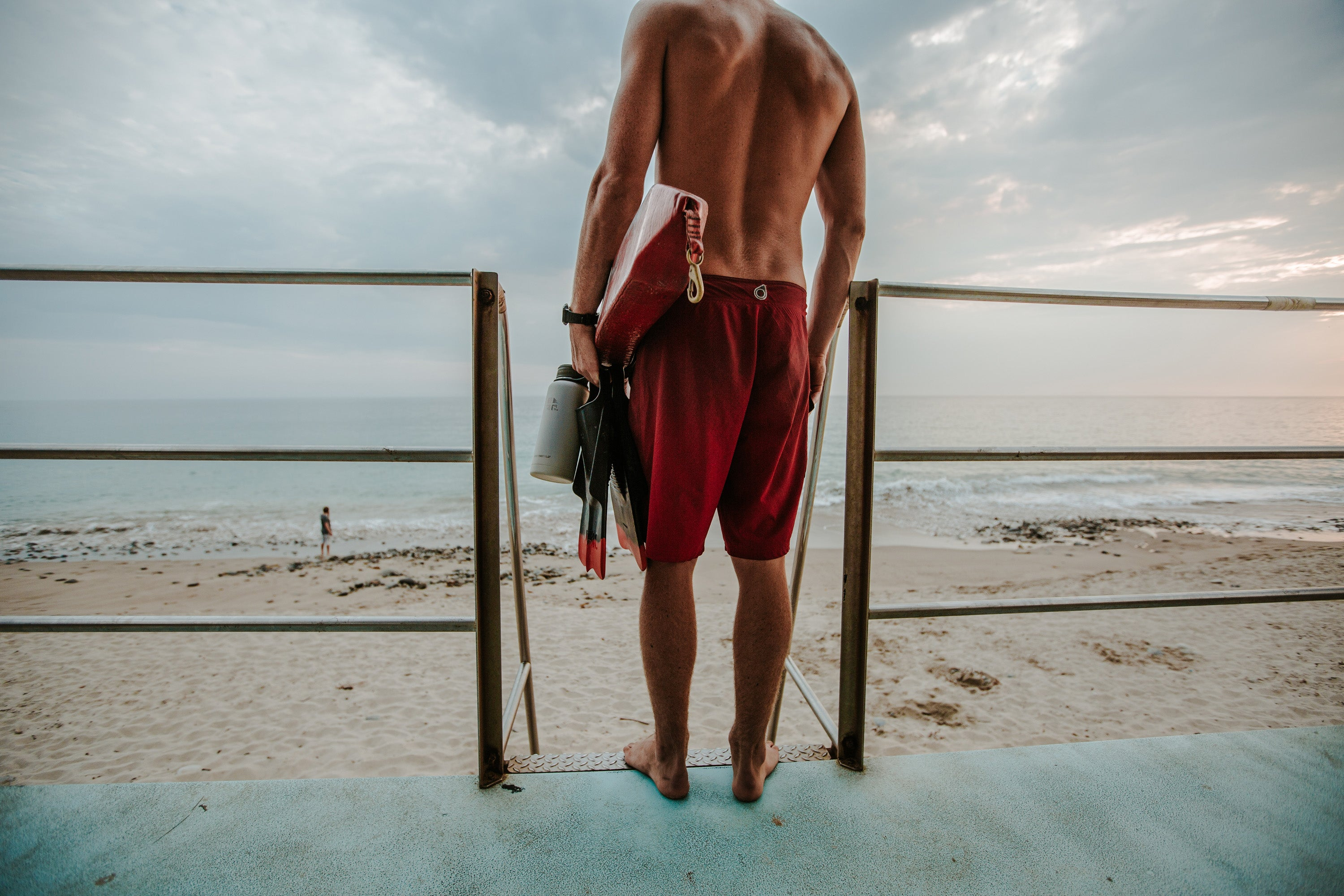 Man standing on beach holding a surf board and an Earthwell Kewler Insulated Water bottle - designed to keep your cold drinks cold for when surfs up.