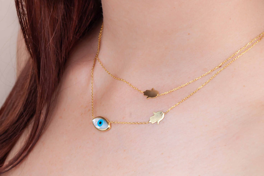 Gold plated mother of pearl amulet and eye necklace worn on neck