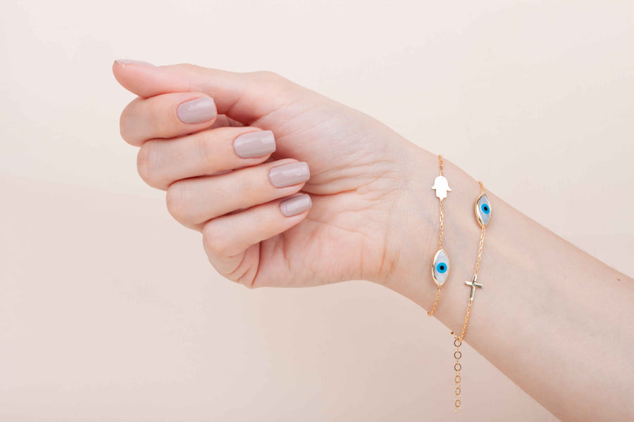 Gold plated mother of pearl cross and eye bracelet worn on wrist