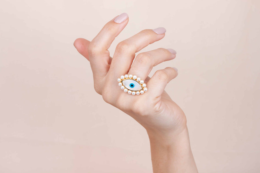 Gold plated mother of pearl eye ring with pearls worn on finger
