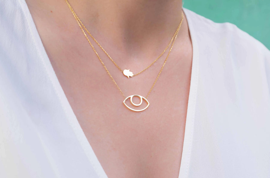 Gold plated abstract eye necklace worn on neck