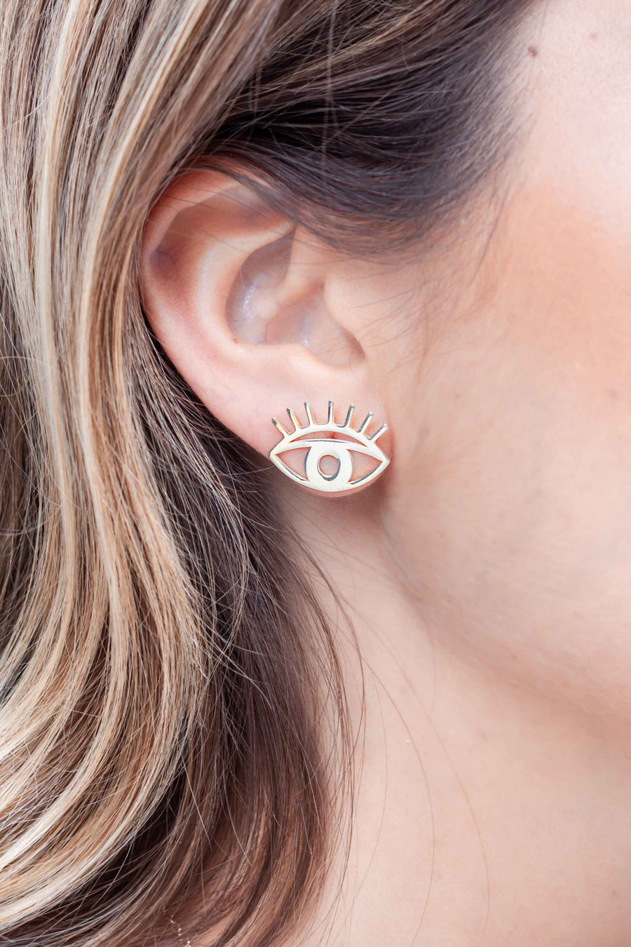 Gold plated abstract eye studs worn on ear
