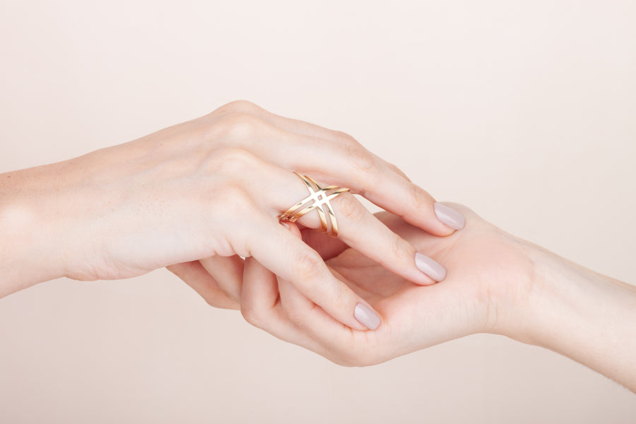 Gold plated crossed ring worn on finger