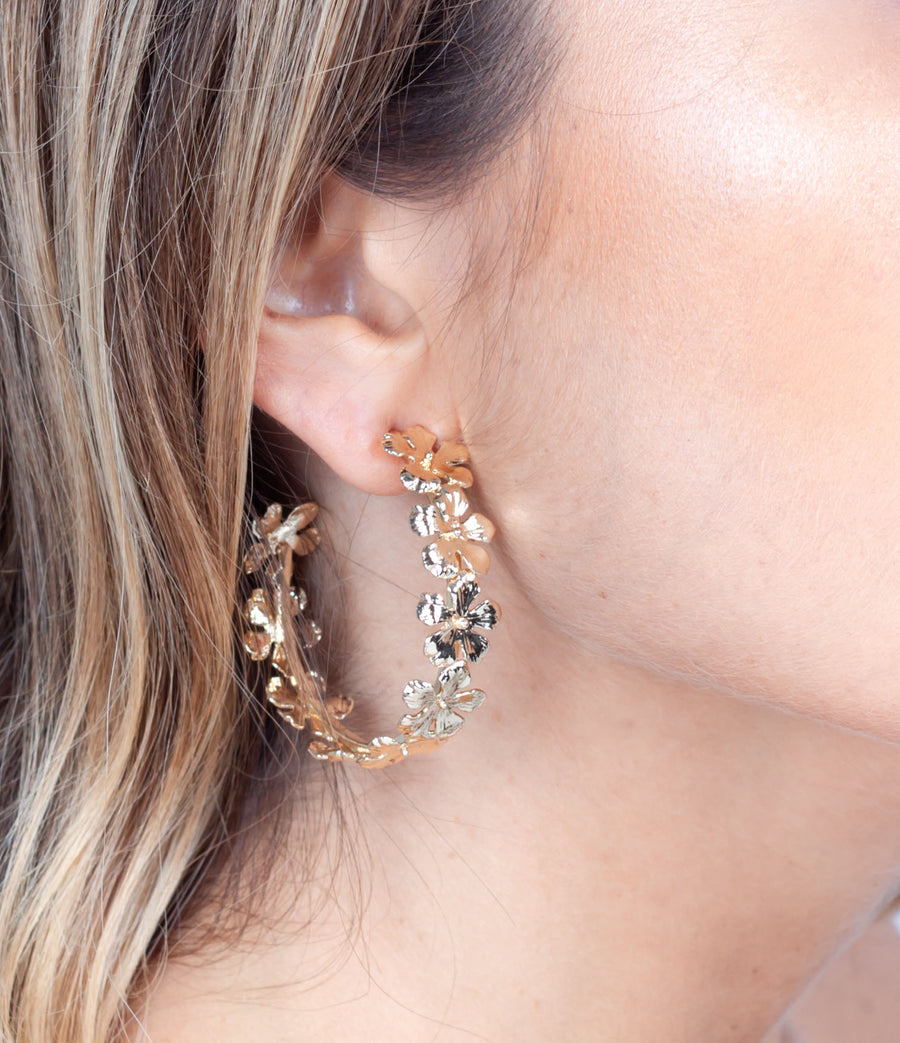 Gold plated flower hoop worn on ear