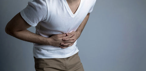 Man holding stomach, presumably due to a gastric ulcer