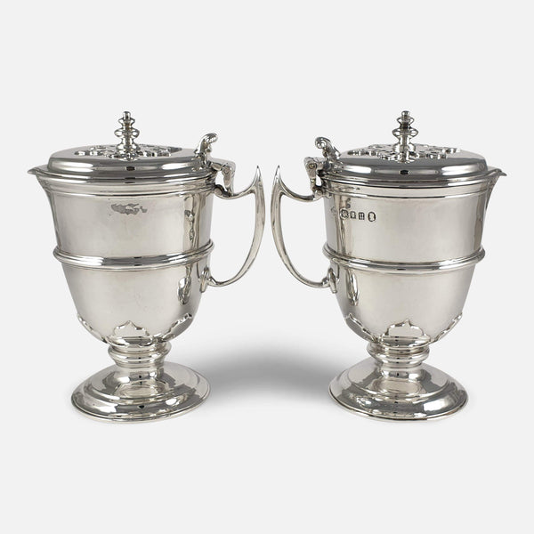 The pair of sterling silver jugs facing in opposite directions