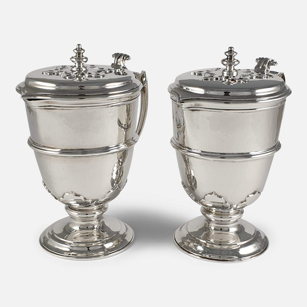 the silver jugs viewed from an angle both facing in the same direction
