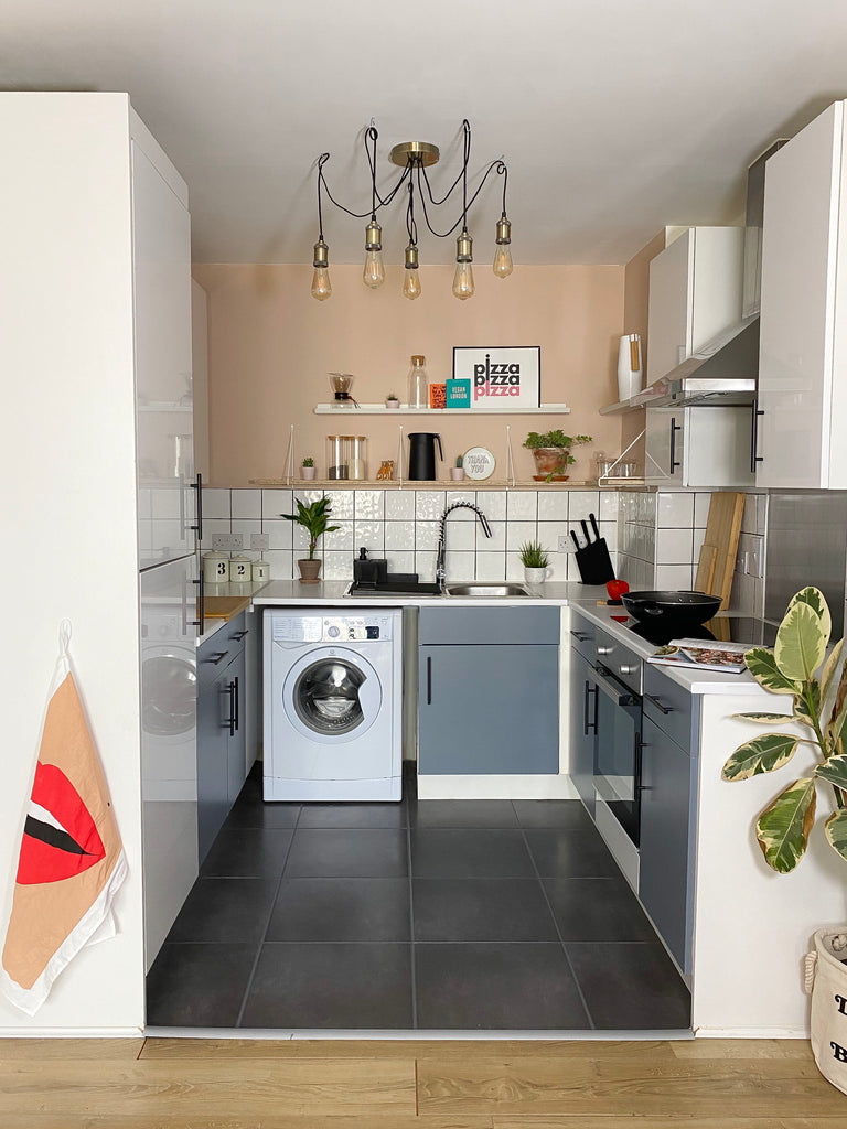 Tiny kitchen with white tile backsplash and chandelier