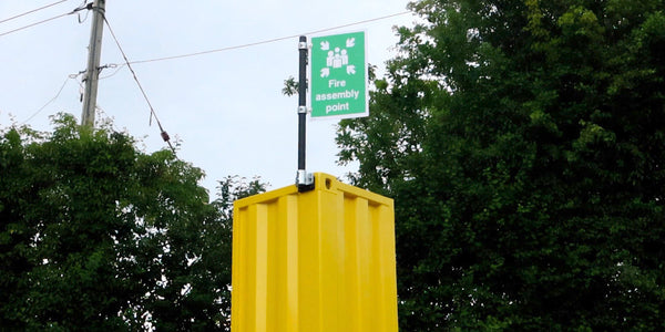 A safety sign mounted securely to the top of a shipping container