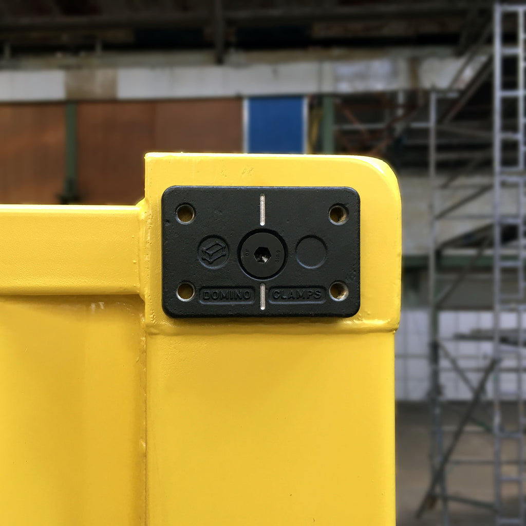 Front view of Domino Clamp attached to a shipping container