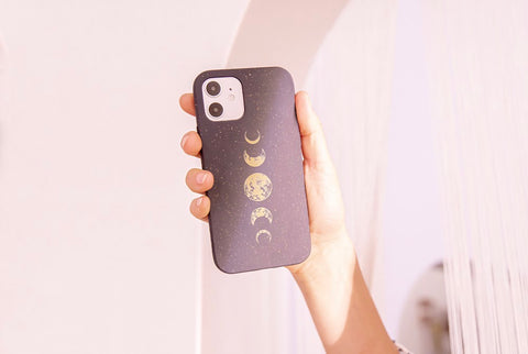 woman holding up phone case with moon design