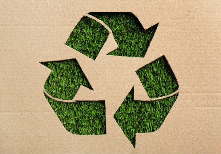 Sheet of cardboard with cutout recycling symbol on green grass