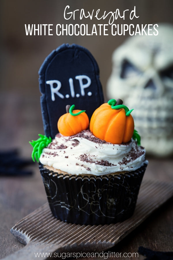 A spooky Halloween cupcake recipe that's not too scary, these White Chocolate Graveyard Cupcakes feature a spooky graveyard scene made of fondant perched on top of homemade white chocolate buttercream.