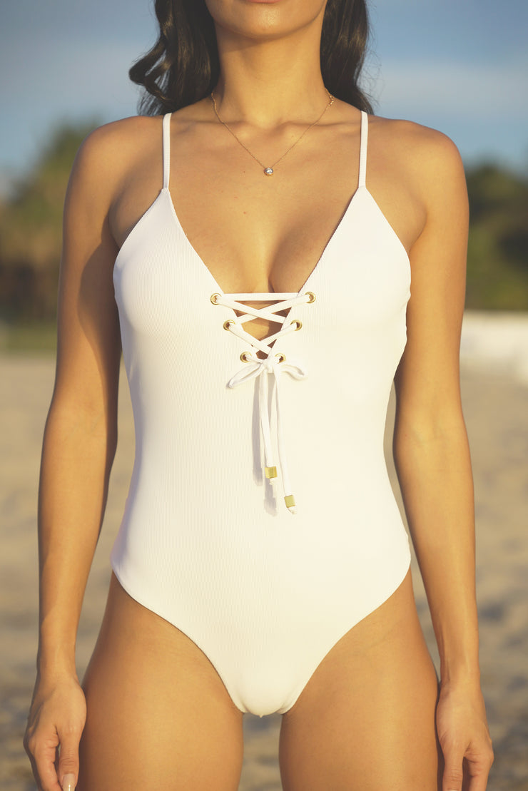 One piece ribbed white swimsuit triple lined. Features a lace up front and strappy sexy back with gold hardware and adjustable straps.