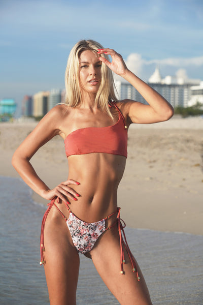 asymmetrical one shoulder strap bikini top with gold tie ends made from sustainable fabric and printed bikini bottom with side ties made from sustainable fabric in floral and animal print.