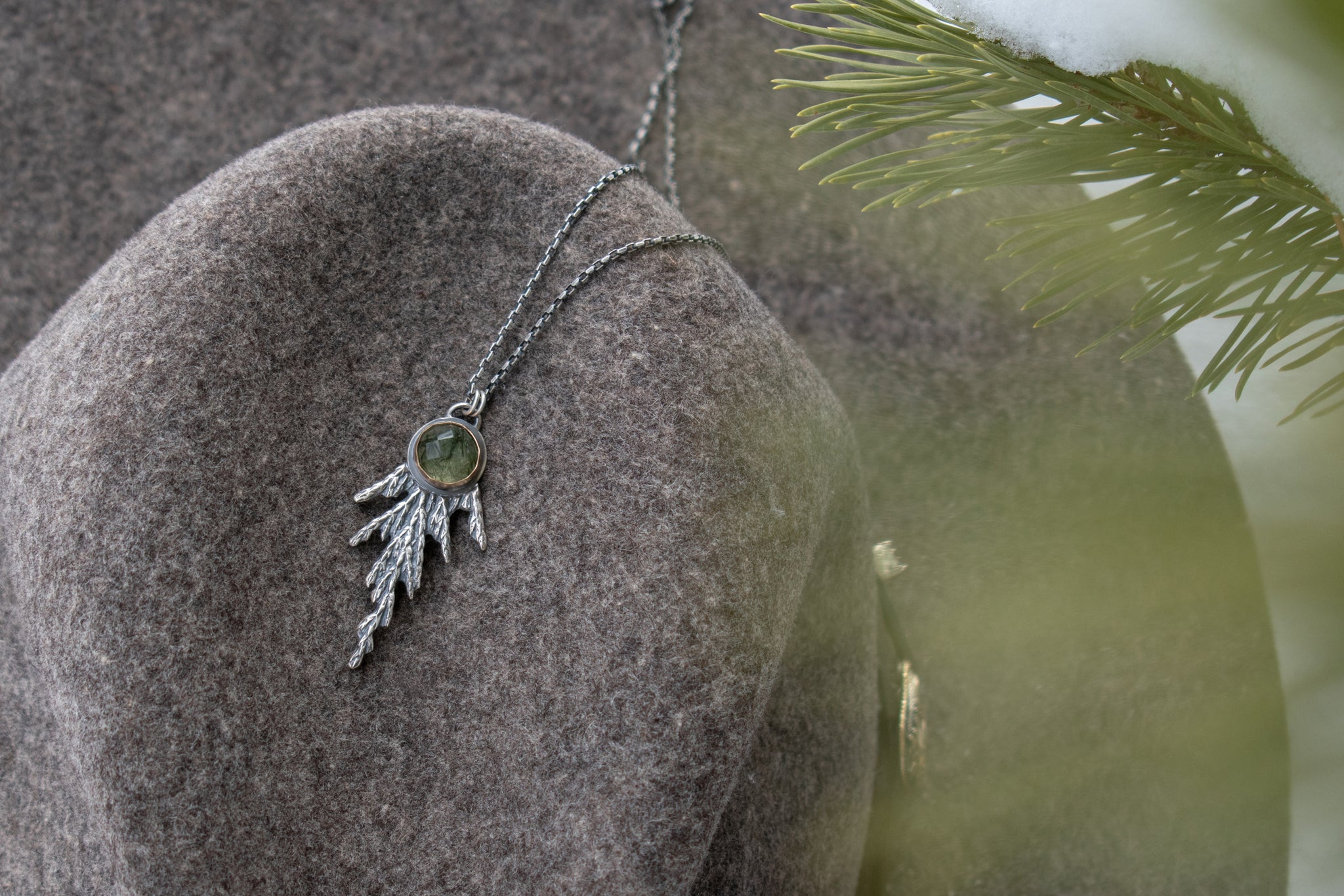 Handmade sterling silver cedar necklace with green stone set in 14k gold draped on women's hat with evergreen in foreground