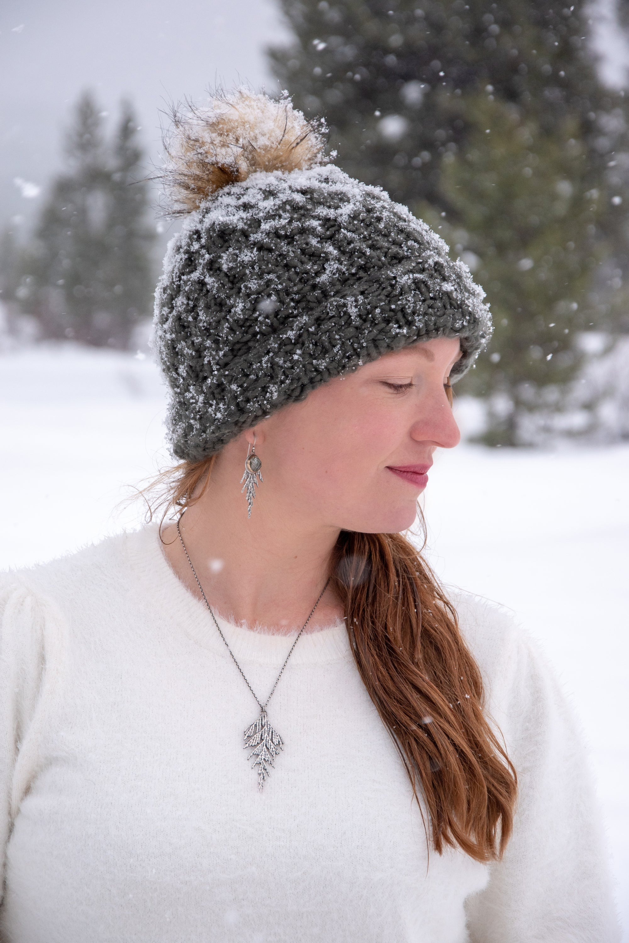 Woman wearing silver and gold cedar jewelry in winter