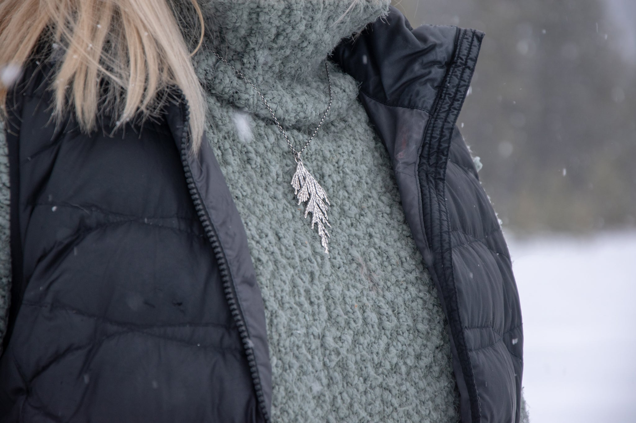 Woman wearing handmade silver cedar necklace in winter