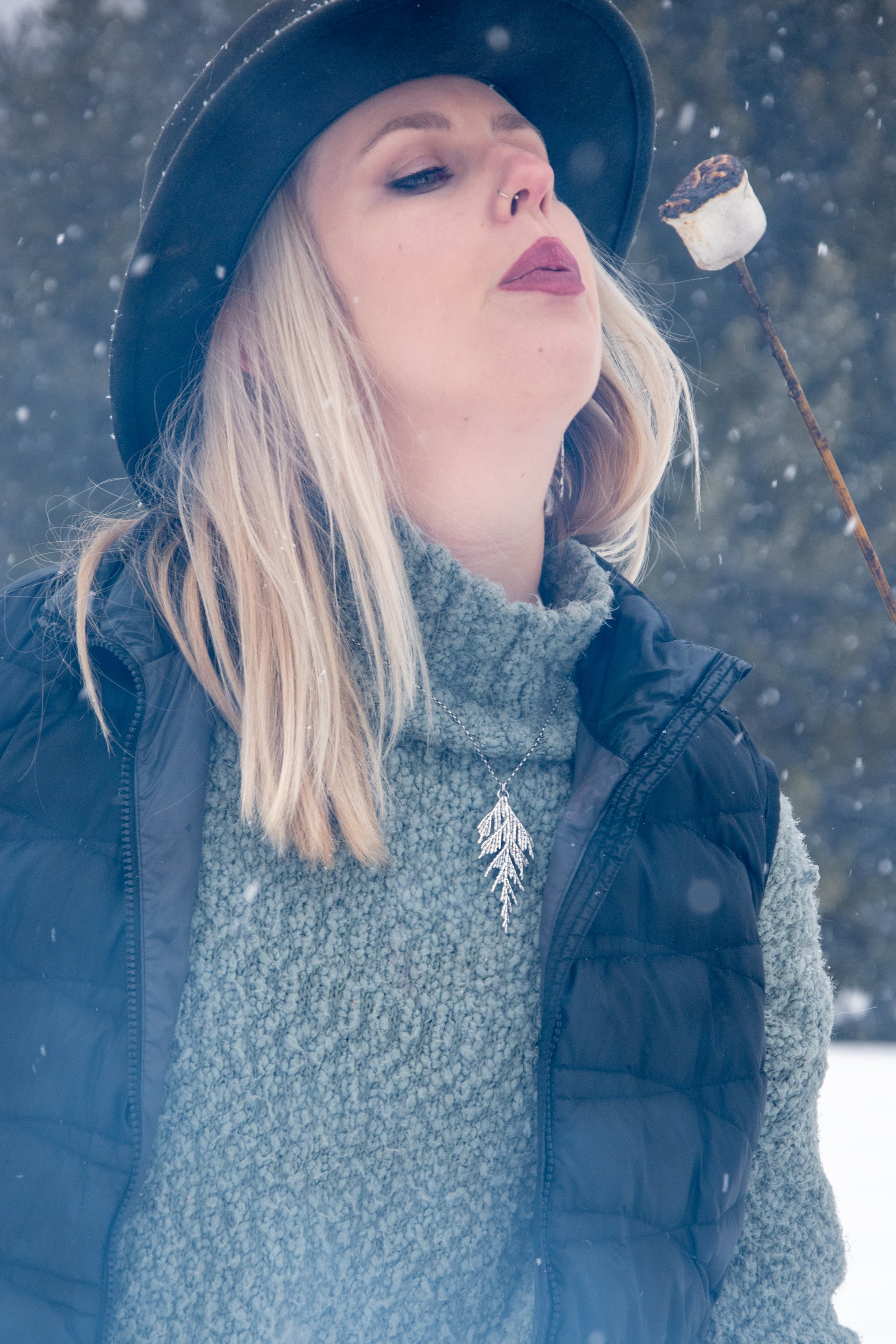 Woman wearing handmade silver cedar necklace while blowing on hot marshmallow in winter