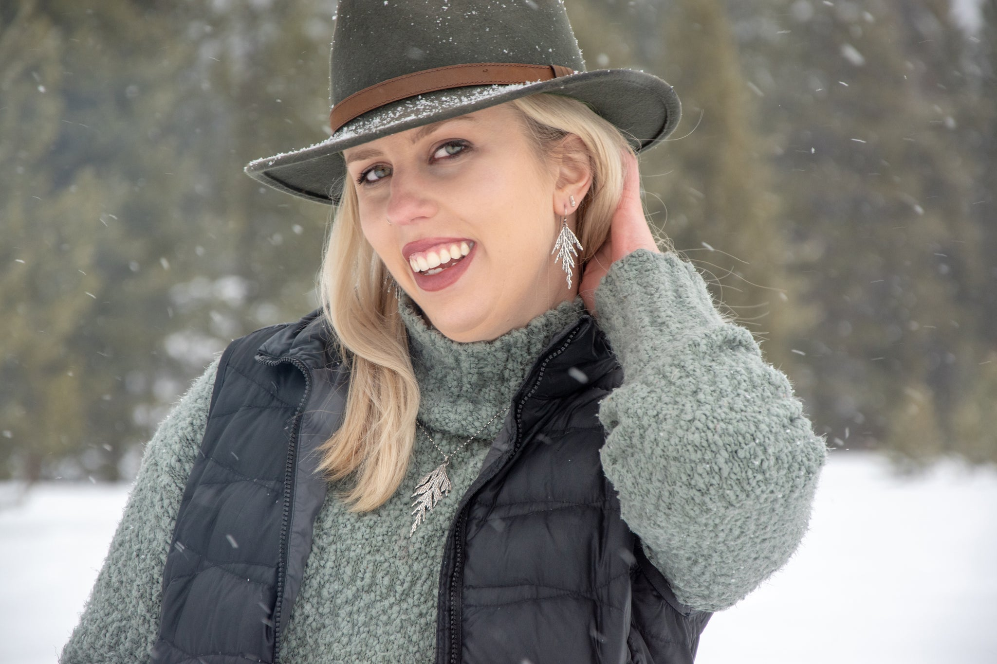 Woman wearing silver cedar earrings in front of snow and pine trees